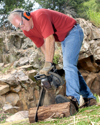 Photo: Man cutting log with protective eyewear