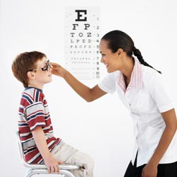 Optometrist giving young boy an exam