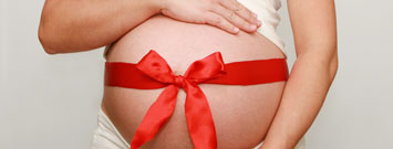Photo: Pregnant woman with Christmas bow on belly