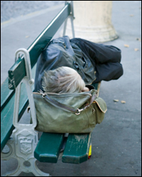 Photo: A person sleeping on a park bench.