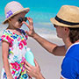 Father putting sunscreen on daughter's nose