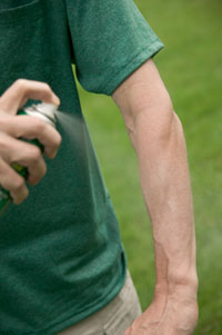 Photo: Man spraying insect repellent on arms