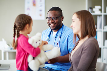 Doctor talks with young patient and mom