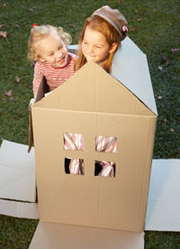 Photo: Two girls inside cardboard playhouse