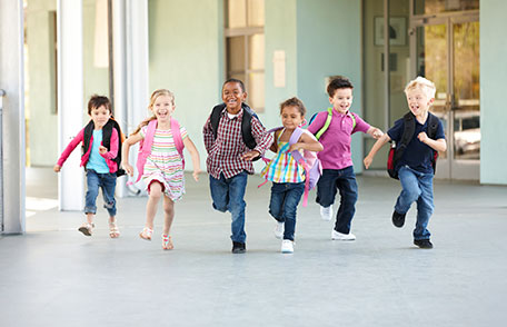 Group of children running down school hallway