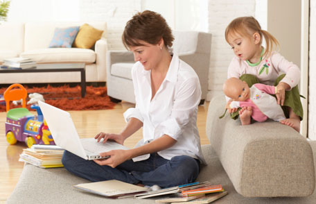 Mother using laptop while daughter plays with toys behind her
