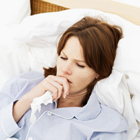 What to do if you get sick with the flu. Photo of woman in bed coughing.
