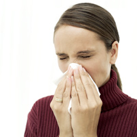 Photo of woman sneezing as part of having seasonal flu.