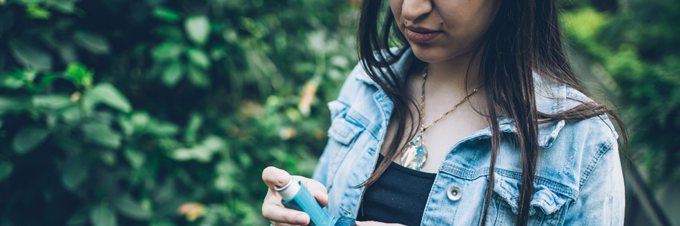 mujer en un bosque sosteniendo un inhalador