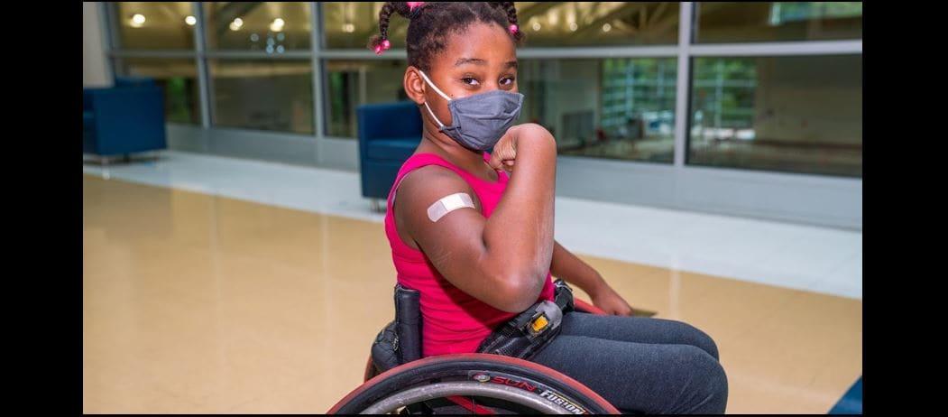 Niña en silla de ruedas luego de recibir la vacuna contra la influenza