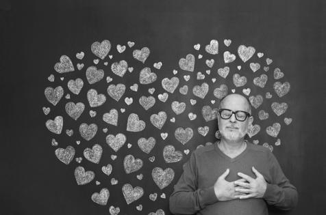 Un hombre parado en frente de una pared con corazones
