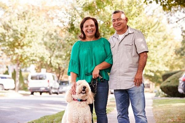 Foto de una pareja de adultos mayores paseando al perro por una calle suburbana