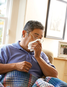Coughing can help clear congestion when you are sick with the flu. Cover your cough with a tissue, like this man.