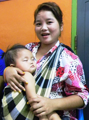 In Laos, a young mother and holds her baby and receives information about seasonal flu.