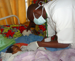 An influenza surveillance nurse collects a sample from a child with acute respiratory illness at a local hospital in Rwanda.