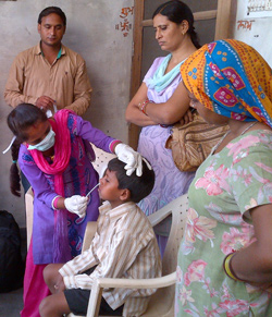 A nurse in India collects a sample from a young boy's nose as part of a house-to-house surveillance study on influenza vaccine.