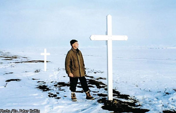 A picture of Johan Hultin at the Brevig Mission gravesite in 1997, 46 years after his first attempt to rescue the 1918 pandemic flu virus. Hultin saw that the small crosses that previously covered the site were missing, so Hultin built two large crosses (shown above) within the woodshop of a local school to mark the gravesite. Photo credit: Johan Hultin.