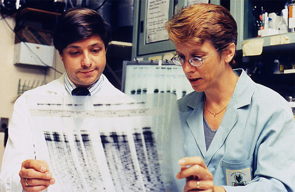 A picture of Dr. Jeffery Taubenberger and Dr. Ann Reid reviewing a genetic sequence from the 1918 virus. They are credited with sequencing the genome of the 1918 virus. Photo Credit: National Museum of Health and Medicine Online Exhibit - MIS 377212.
