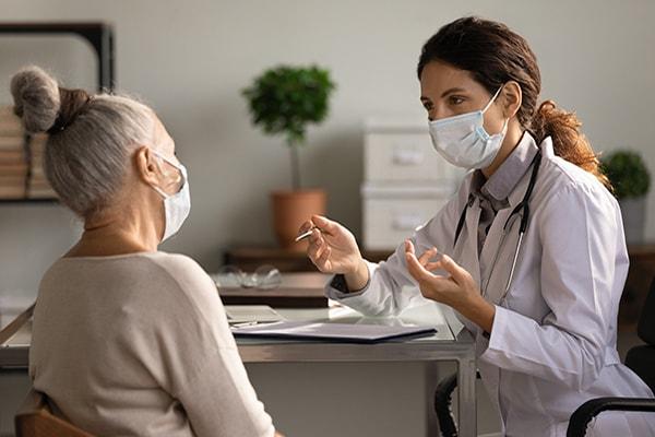 Médica hablando con un paciente mayor, ambos con mascarilla.