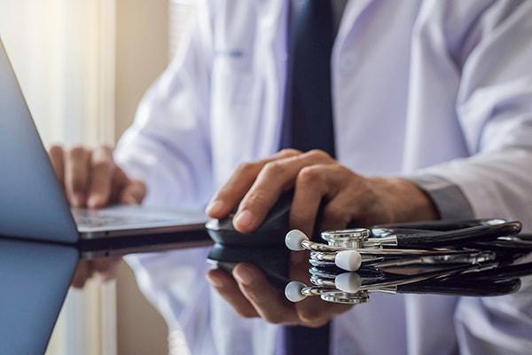 Médico trabajando en su computadora con un estetoscopio sobre el escritorio.
