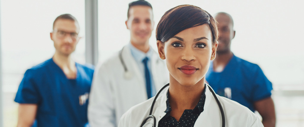 confident female doctor in front of team