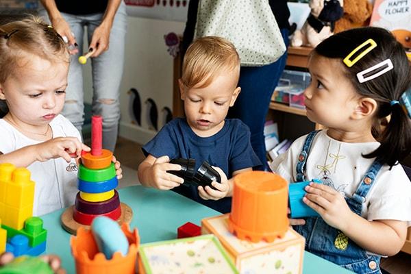 Niños de una guardería jugando con la maestra en el salón de clase