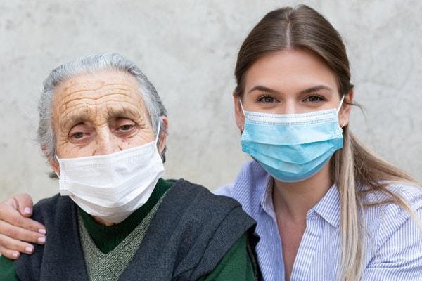 mujer mayor y mujer más joven juntas usando mascarillas