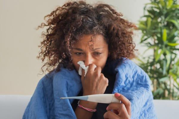 mujer estornudando en un pañuelo desechable y mirando un termómetro
