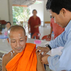 Dr. Anonh, Director of the National Immunization Program for Lao Ministry of Health, administers flu vaccine during a clinic in rural Vientiane.