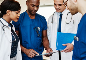 Photo: health care professionals discussing a patient's chart