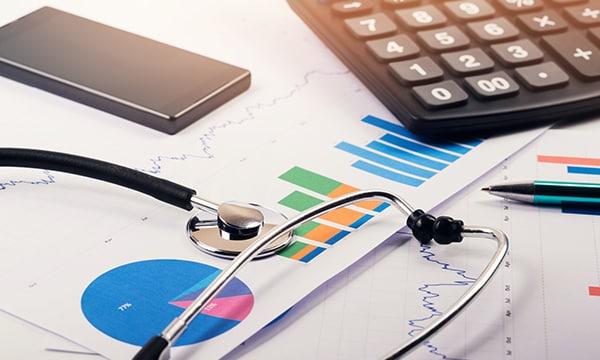 Un estetoscopio, una calculadora y un informe de datos sobre un escritorio