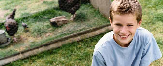 Un niño parado frente a aves de corral domésticas (pollos).