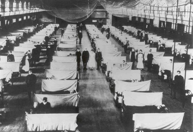 Cots set up in gymnasium for flu patients