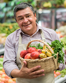 Grocery store owner with basket of vegatables