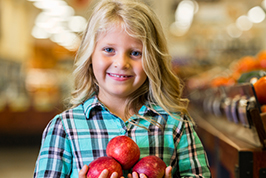 Little girl with apples istock 78305351