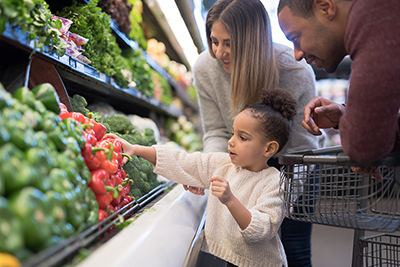 Image of a mother and father with their younger daughter shopping for healthy vegetables