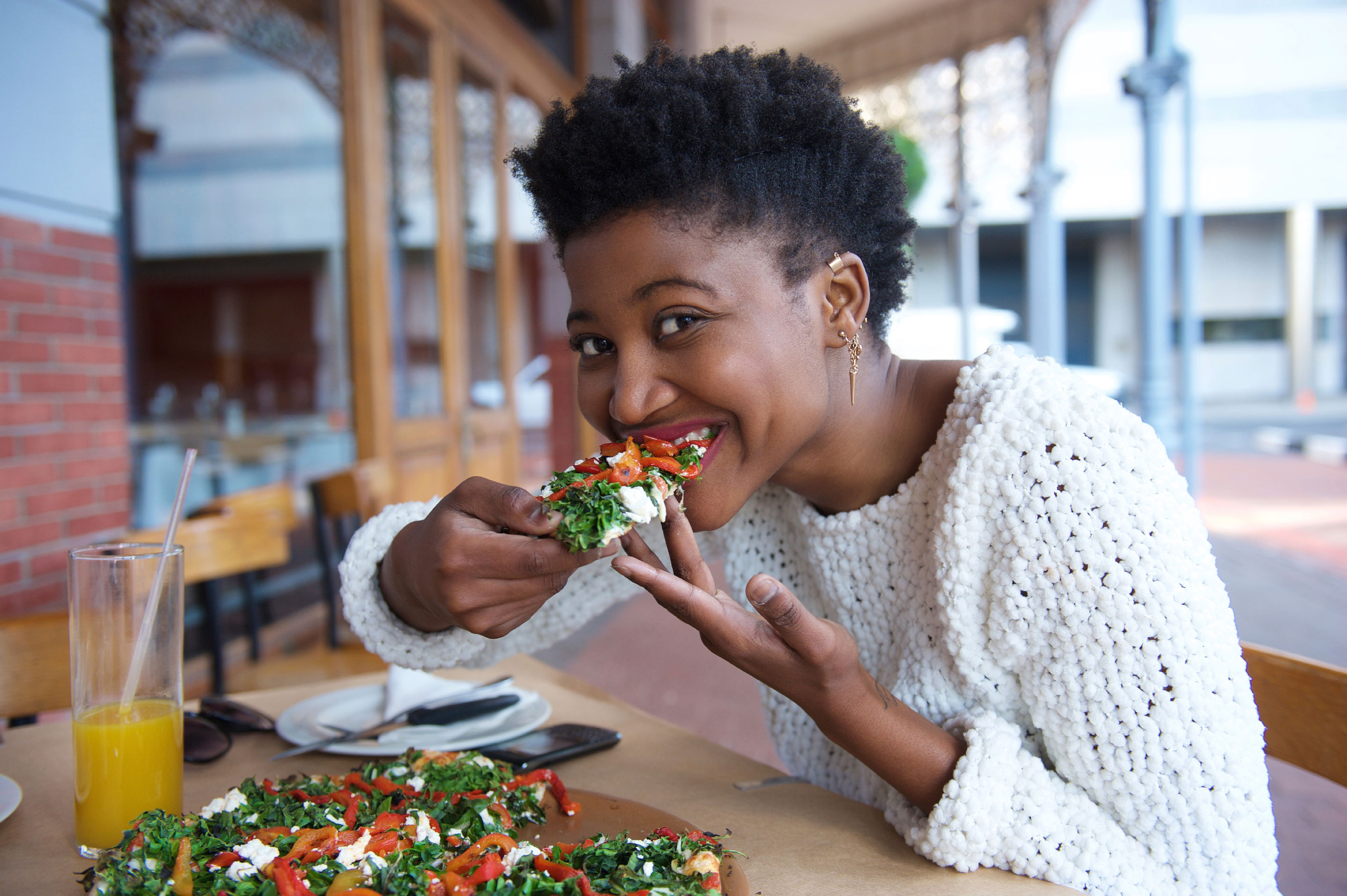 Young woman eating vegetarian pizza