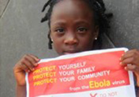 Little girl holding an ebola poster.