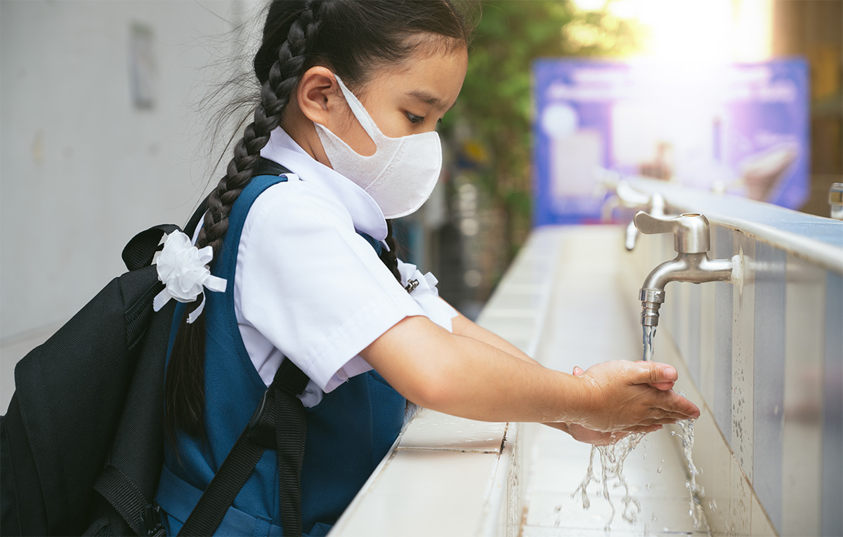 Image of a girl wearing a mask while she washes her hands in a school bathroom sink