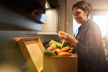 Image of a woman in a kitchen with a full box of vegetables