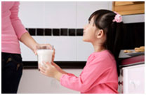 mom handing milk to girl