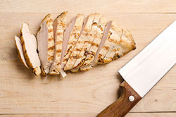 Cut chicken breast and knife on cutting board