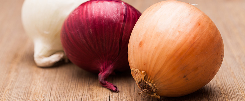 Photo of three differently colored onions on wood.