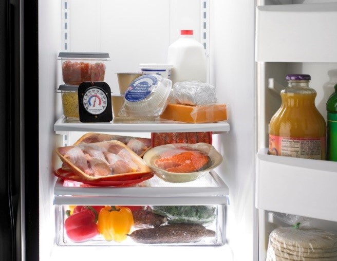 PHoto of a refrigerator with common graceries found inside including fruits, vegetables, and various meats.