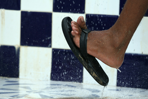 Foot with flip-flop in shower.