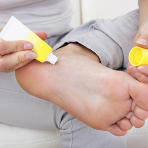 Woman applying cream to her foot.