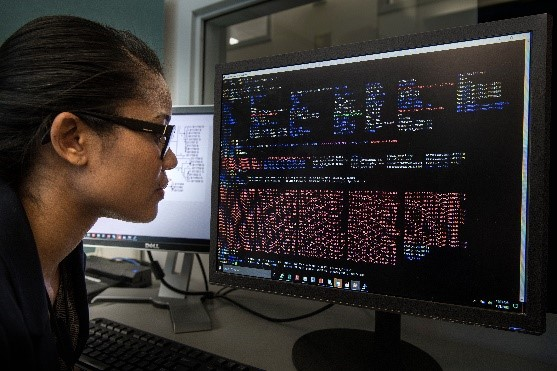 A woman analyzing whole genome sequencing data on a computer screen