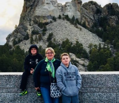 A woman standing with her 2 sons in front of Mount Rushmore.