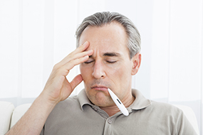 Man with thermometer in his mouth while holding his head.