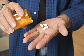 Man pouring pills in hand.